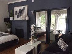 Use white accents and mirrors opposite a window to brighten up a dark-painted room