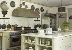 I like the mix of metals in this kitchen - from industrial light fixtures to st.st. to silver