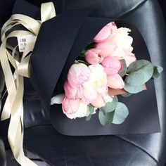 a bouquet wrapped in black makes the flowers stand out.