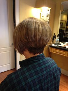 Light brown hair with natural honey colored highlights. Cut into an inverted bob and a close tapered neck
