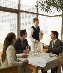 Waiter handing business people menus at restaurant table - Chris Ryan/OJO Images/Getty Images