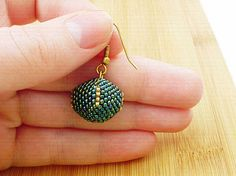 Guľôčka obšívaná smaragdovými a zlatými korálkami.