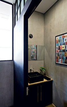 A luz natural entra pela vidraça junto ao teto do lavabo, no apartamento decorado pela designer de interiores Elena Arruda. As paredes receberam tinta que imita cimento queimado