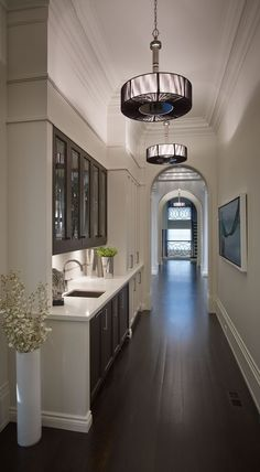 A servery of classic proportion and asymmetric materials arrangement. In the mix is rich walnut door fronts with an envelope of gallery white.  Designed by Regina Sturrock Design Inc.