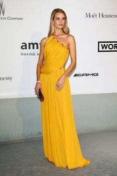 De la Gala amfAR: Rosie Huntington-Whiteley. Con un vestido asimétrico color azafrán de Emilio Pucci otoño 2014.