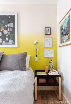 Quarto de casal com papel de parede em degradê amarelo, criado-mudo preto, muitos quadros e almofadas cinzas.