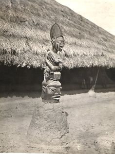 Nigeria, carved wooden mask placed on mound of earth. Mask surmounted by figure which appears to represent adult female carrying young child, smaller figure [child?] standing at her side. Single-storey thatched-roof building in background. Medium: Gelatin silver print.