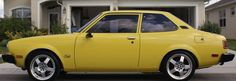 1976 or 77 Dodge Colt. Bright yellow with a blacked-out grill & slightly different aluminum alloy wheels. Economical commuter.