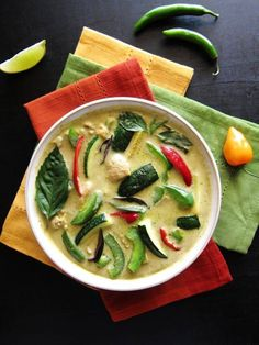 Instant Pot Thai Green Curry with Chicken with colorful vegetables in white bowl, on three colorful napkins. Lime slice and chili peppers on black background- Paint the Kitchen Red