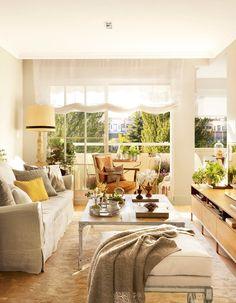 Salón con grandes ventanales con estores blancos, sofá con funda blanca y mesa de centro de madera decapada