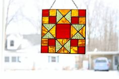 This is a beautiful Ohio Trail quilt block pattern which was made using a steaky red/orange stained glass for the center block and corners, a wavy amber stained glass for the alternate color and a textured olive green stained glass for the other alternate blocks. It measures 7 3/4 x 7 3/4 and is framed in zinc. I have attached a chain for hanging and will supply a suction cup.  This would be a beautiful addition to any window in your home.  All items in my shop are handmade by me in my home…