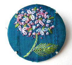 Art embroidery silk hydrangea brooch by MargDierEmbroidery. french knots and lazy daisy stitches on a turquoise silk backing.