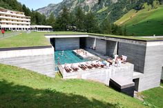 The Therme Vals / Peter Zumthor 1996. A hotel/spa in Switzerland. Half-buried in the hillside, with grass roof, like an archeological site.