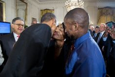 President Obama gives a cheekie to Joane Wise and her son Terrance Wise is standing there watching