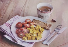 """Breakfast Blog - Morning Diaries - Scrambled tofu"""", with cherry tomatoes a slice of sourdough rye crisp bread with peanutbutter, and a cup of yogi tea with chocolate flavor."""