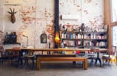 loft with long table, eclectic chairs, painted brick, high ceilings and big bookshelf