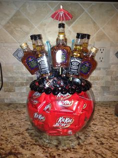 Whisky & Chocolate Bouquet (Liquor Bouquet).  Hot glue beads around rim of bowl.  Put florist foam in bowl and place candy around foam to cover sides.  Hot glue liquor bottles onto wood skewers (so body of bottle is supported by skewer but neck is not).  Stick them in the foam to make a bouquet--3 Jack in back, 3 crown in middle, 2 Jack in front.  Stick stir sticks in between.  Glue umbrella onto middle bottle in back.  Place curly ribbon over top of foam to cover it. #liquorbouquet