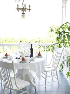 This airy porch looks laid-back and relaxed thanks to an all-white color palette and a pair of traditional chairs. A small, round table with a simple white tablecloth brings the slightest amount of formality to the space. A petite chandelier helps to illuminate the scene after the sun goes down.