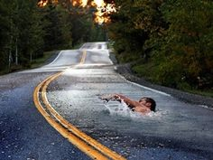 Wallpaper Man swims in the road as the water surrealism