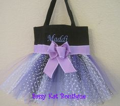 "This fun little tote bag makes a great purse, dance bag, flower girl tote or carrying case for e-readers/tablets. The bag measures 9"" x 11"" with a 3"" bottom gusset. The bag is made of sturdy canvas and the tutu is hand made from several layers of polka dot and purple tulle and sewn on the bag along with the ribbon and big purple bow. The name is embroidered on the bag by machine.FREE PERSONALIZATION; just include the name in the notes on the PAYPAL order form...."