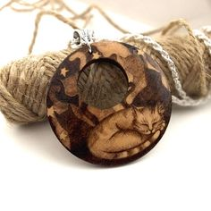 A sleepy cat and friends, pyrography cats pendant. A lovely cat necklace, pyrography jewellery, ideal for a pet lover, and a great nature lover gift. Fab for a wood anniversary (5 years marriage).  The image and composition are my own, drawn freehand onto the wood. I use no templates or transfers. Each piece is unique. The pendant measures approx. 5 centimetres in diameter and is slightly domed. After the design is completed, it is sealed with varnish to help protect it. Wood wears over…