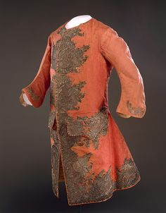 Sleeved waistcoat, fabric: England, garment: America, c. 1759. Flame-orange figured silk with an abstract feather/scroll and leaf design. The dense embroidery consists of silver metallic threads over stiffened paper scroll cut-outs, appliquéd onto the ground fabric, silver buillion embroidery, pailletes and flattened strips decorate the wooden buttons.