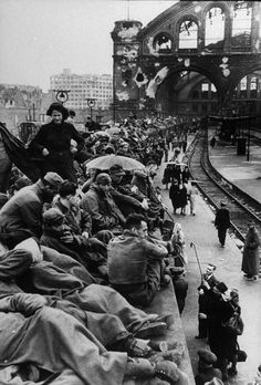 Throngs of German citizens crowd the platforms of the Berlin train station shortly following the defeat of Germany by Allied forces. The crowd is made up of displaced citizens of the city caused by bomb and battle damage trying to flee the city,...