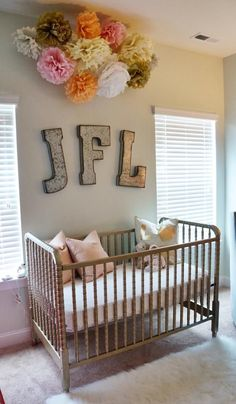 We love tissue poms over the bed in place of a mobile - so whimsical and perfect for a nursery!