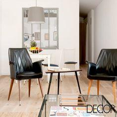 Em um ambiente contemporâneo, a dupla de cadeiras de pés em madeira e encosto e assento em tom escuro compõe de forma harmônica este espaço