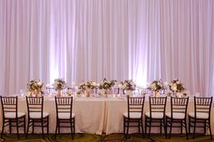 Hotel Ballroom Gold and White Wedding Reception Long Feasting Table with Black Chiavari Chairs, Low white and Greenery centerpieces in Gold Vases with votive candles and white draping | Tampa Bay Historic Wedding Venue The Vinoy