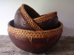 Three nesting bowls trimmed in a wicker weaved honey comb trim. A rich chestnut brown color made from a hard hollowed wood. Turned wooden bowl.
