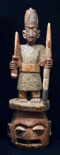"""A Yoruba Epa Mask. Nigeria, mid 20th century. A large and impressively carved superstructure ceremonial helmet mask with a tall imposing figure surmounting the janiform human helmet. The figure atop is adorned with fez headdress, and holding a staff and sword. Elaborately painted polychrome surface. 43-1/2"""" H."""