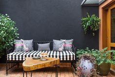 A parede da área externa da casinha foi pintada de preto para minimizar a sujeira. No decor, banco de ferro, almofadas estampadas e mesinha de madeira bruta.