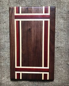 This custom cutting board is made using beautiful maple, walnut and bloodwood. The dimensions are approximately 13 x 8. This one of a kind cutting board also works great as a centerpiece and serving tray. Cutting boards are finished with mineral oil and beeswax. Additional care