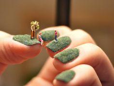 Arte nas mãos – Cenas em miniatura sobre um gramado nas unhas