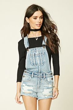 A pair of denim overall shorts featuring a distressed front, a five-pocket construction, burnished buttons, and adjustable straps.
