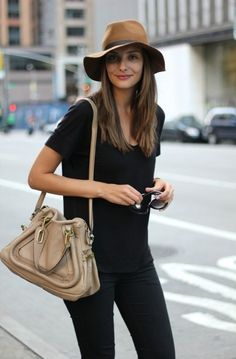 Comfortably chic. Black short sleeved scoop neck tee shirt, long and loose. Skinny black jeans. Tan mid brim fedora with brown grosgrain plus slouchy taupe shoulder bag. Glasses in hand. Style Planet