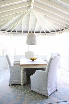 But with a fresh coat of white paint, all of these architectural features come to the fore. The new look creates the perfect setting for the rustic dining table, crisp slipcovered chairs, sheer curtains, and the simple wicker pendant.