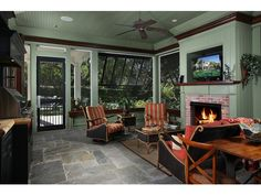 Elegant screened lanai with fireplace and outdoor kitchen in this Olde Naples, FL home.