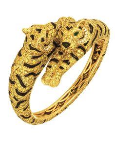 Veronique Bamps : Très rare bracelet signé Cartier Paris; en or jaune 18K, entièrement serti de diamants taillés en brillant de couleur jaune intense (fancy intense yellow), de quelques diamants blancs sur les joues, les rayures en onyx et les yeux en émeraudes. Ce bracelet est rare car il figure deux tigres, les exemples connus sont avec un tigre unique. Leurs têtes pivotent légèrement