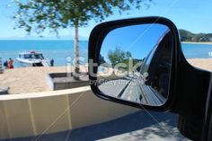 Looking at the view from a car mirror. The scenery surrounding is Kaiteriteri Beach in the Abel Tasman National Park, New Zealand in blur. Selective focus is on the view in the reflection. Car Mirror, Rear View Mirror, Abel Tasman National Park, The World Race, Reflection Photography, Kiwiana, New Zealand Travel, Turquoise Water, Travel And Tourism