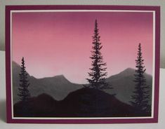 By Loll Thompson. Masked mountains. Brayered onto glossy cardstock: Regal Rose, Rich Razzleberry in sky area. Masked sky. Brayered mountain area with Basic Gray. Then tore another mask to cover distant hills & brayered with Basic Black. Heat set or let dry completely. Stamp trees in black. Heat set or let dry. Mount onto frame & card base.