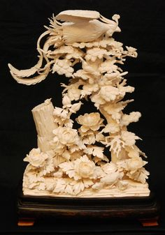 A large Chinese carved ivory phoenix group. Intricately crafted to depict an earth form base with sprawling lotus blossom flowers. A chicken and four chicks can be seen walking around amongst the leaves and flowers. A tall stump to left and pine tree to right can be seen with a large phoenix bird perched atop the tree with wings up. To its back is lingzhi mushroom.