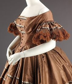 1858-1859 dress with densely gathered sleeve flounces with fringe and 2-flounced skirt triple box pleated at waist. MET