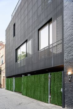 Black zinc cladding and a white sinuous staircase feature in the renovation and expansion of an urban masonry building by New York studio Young Projects.