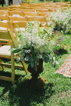 white flowers and greenery in an urn vase for aisle decor