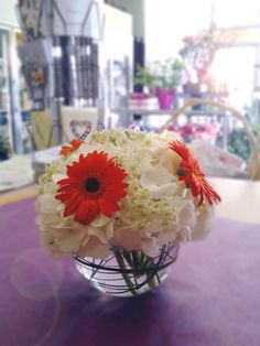 Centre Piece  (Orange Mini Gerbs, Queen annes lace and some white Hydrangea with bear grass looped into the bubble vase)