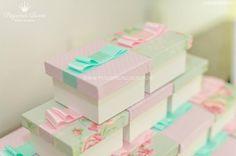 Caixinhas decoradas para os convidados levarem doces pra casa. Mistura de cores da palheta da identidade visual - rosa e azul.