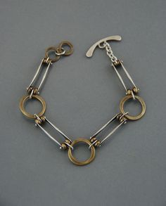 This fun mixed metal bracelet is made from alternating links of forged brass rings, and forged silver bars. They are connected with my signature