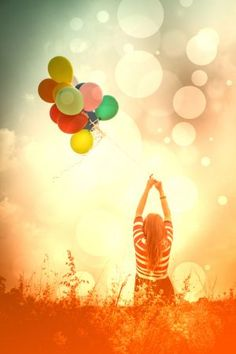 letting go of colorful balloons in a field